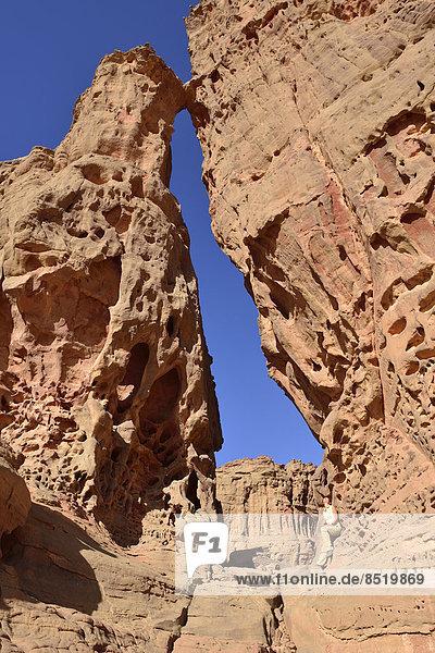 Algerien  Sahara  Tassili N'Ajjjer Nationalpark  Tassili Tadrart  Frau sitzend auf einem Felsen des Kar