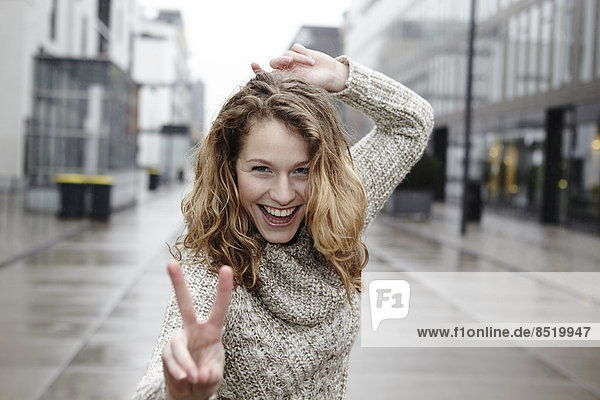 Portrait of happy young woman showing ßictory sign