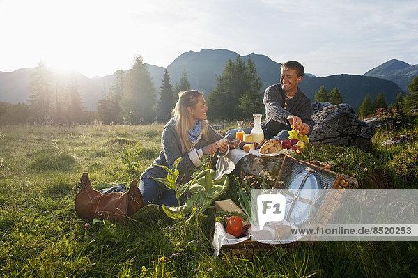 Österreich  Salzburger Land  Altenmarkt-Zauchensee  Pärchen beim Picknick auf der Alm