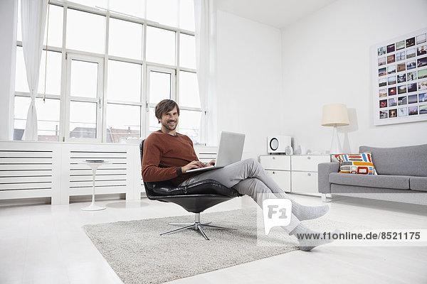 Mann zu Hause sitzend im Stuhl  mit Laptop