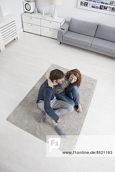 Germany  Munich  Couple sitting on floor in lißing room