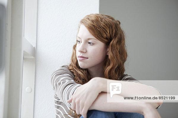 Frau  die aus dem Fenster schaut