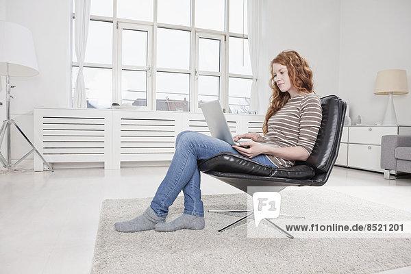 Frau zu Hause  im Sessel sitzend  mit Laptop