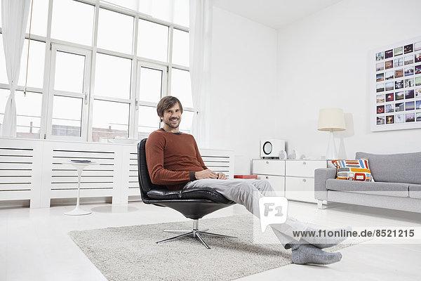 Mann zu Hause  im Sessel sitzend