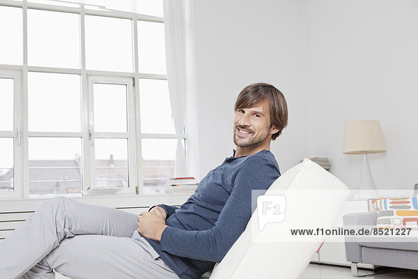 Man sitting on sofa  smiling
