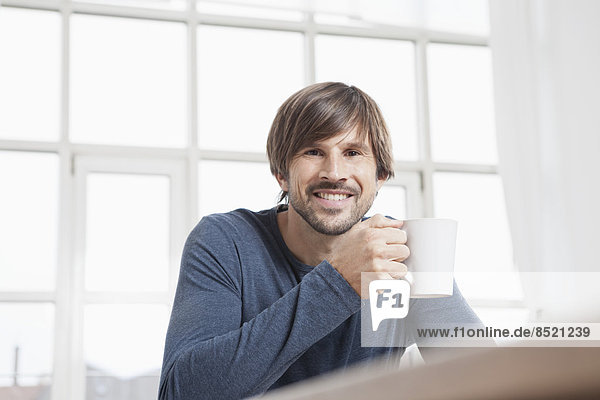 Man sitting at table drinking coffee