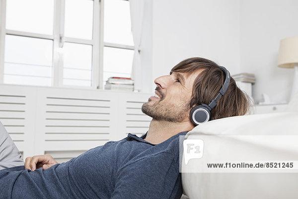 Mann sitzt auf dem Sofa und trägt Kopfhörer.