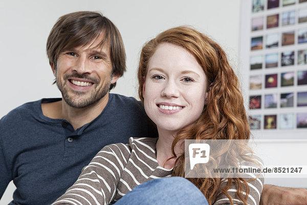 Germany  Munich  Couple sitting on sofa