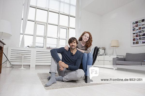 Deutschland  München  Paar sitzend im Wohnzimmer