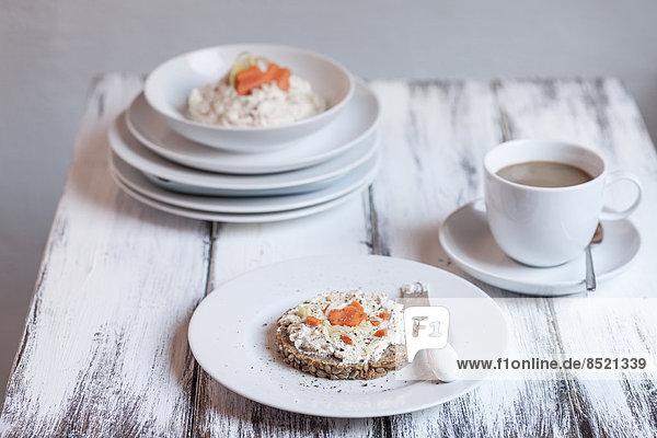 Deutsches dunkles Mehrkornbrot mit Frischkäse und Karotten  Tasse Kaffee auf Holztisch Deutsches dunkles Mehrkornbrot mit Frischkäse und Karotten, Tasse Kaffee auf Holztisch
