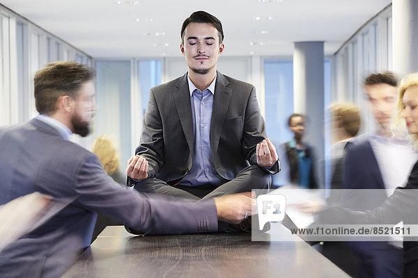 Business man meditating on desk