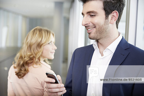 Woman looking at man with mobile phone