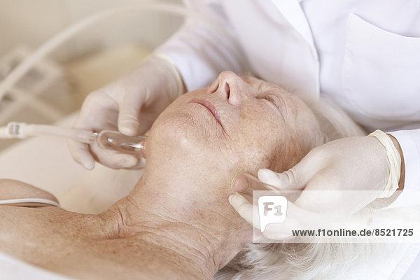 Alternativer weiblicher Therapeut  der ältere Frauen mit einer ß-Vakuumschröpfungstherapie behandelt. Alternativer weiblicher Therapeut, der ältere Frauen mit einer ß-Vakuumschröpfungstherapie behandelt.