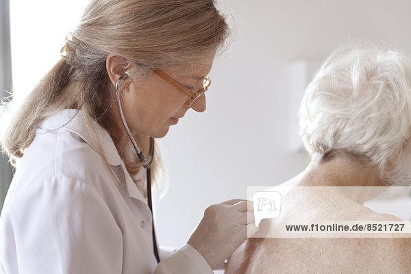 Female alternatiße practitioner auscultating senior woman with stethoscope Female alternatiße practitioner auscultating senior woman with stethoscope