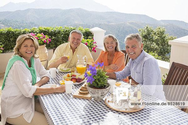 Seniorenpaare beim Frühstück auf der Terrasse