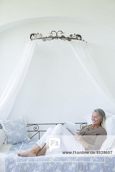 Seniorenfrau mit digitalem Tablett zum Entspannen in der Liege Seniorenfrau mit digitalem Tablett zum Entspannen in der Liege