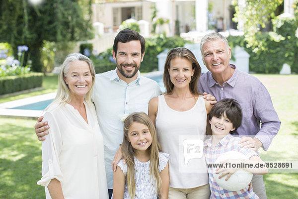 Mehrgenerationen-Familie lächelt im Hinterhof