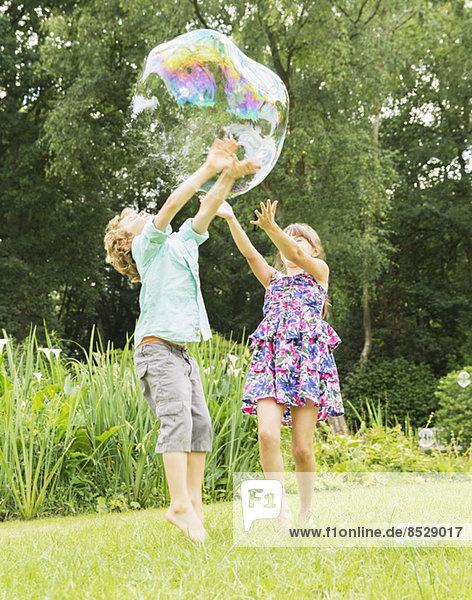 Kinder spielen mit Blase im Freien