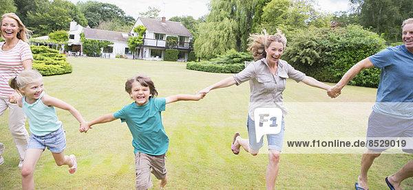 Mehrgenerationen-Familie beim Händchenhalten und Laufen im Hinterhof