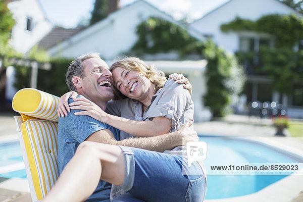 Paar entspannen im Liegestuhl am Pool