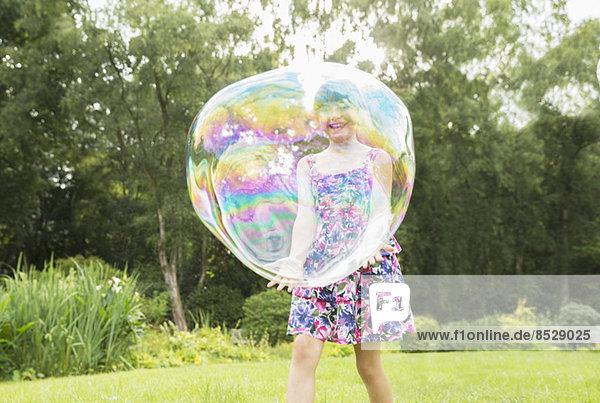 Vater und Tochter spielen mit großen Blasen im Hinterhof