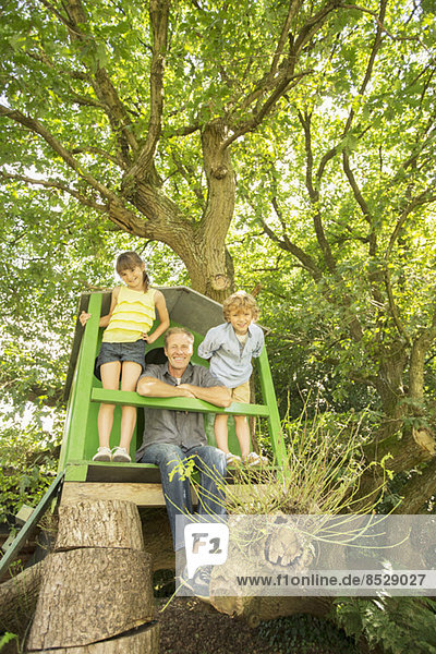 Vater und Kinder spielen im Baumhaus