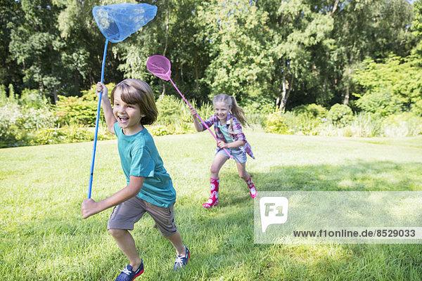 Junge und Mädchen rennen mit Schmetterlingsnetzen im Gras