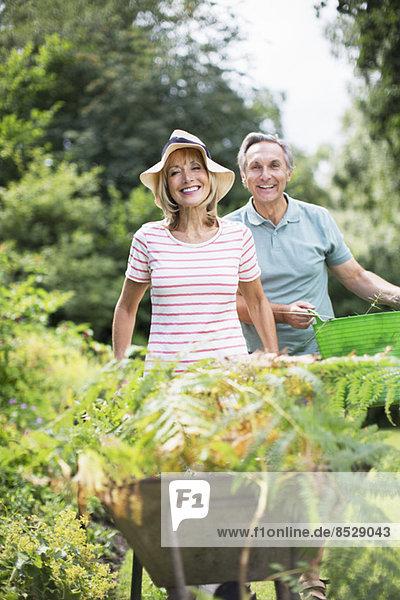 Seniorenpaar mit Schubkarre und Eimer im Garten