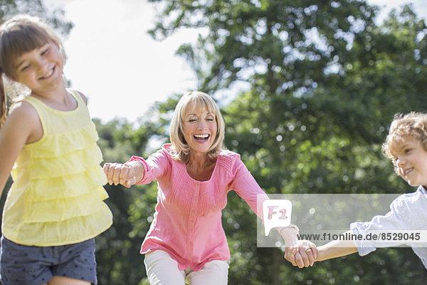 Großmutter und Enkelkinder beim Spielen im Freien