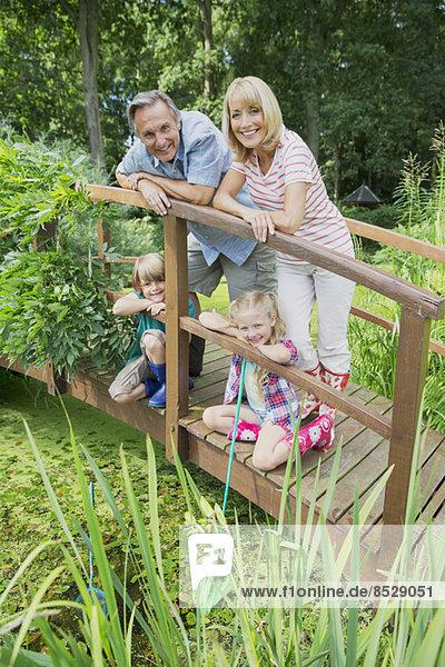 Großeltern und Enkelkinder lächelnd auf Holzsteg