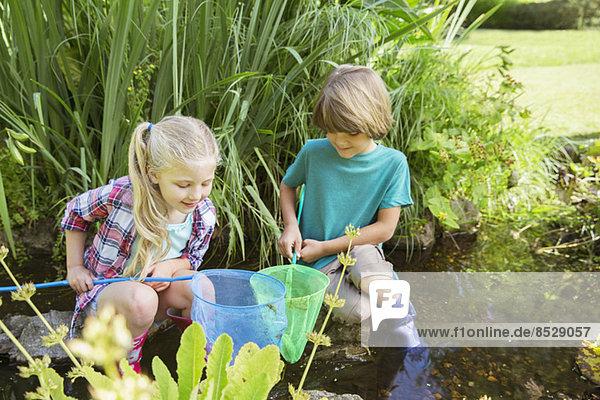Kinder beim gemeinsamen Fischen im Teich