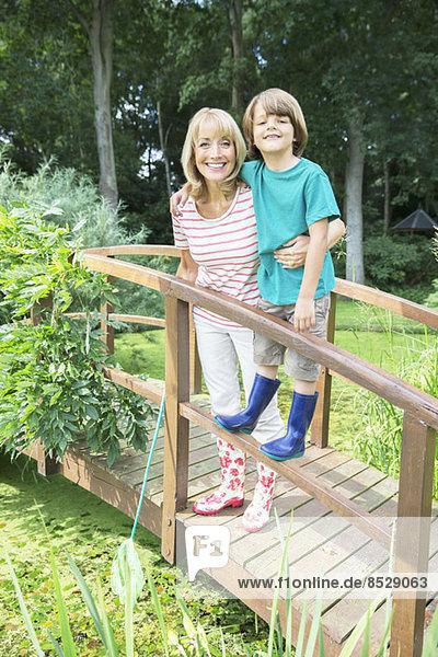 Großmutter und Enkel lächelnd auf Holzsteg