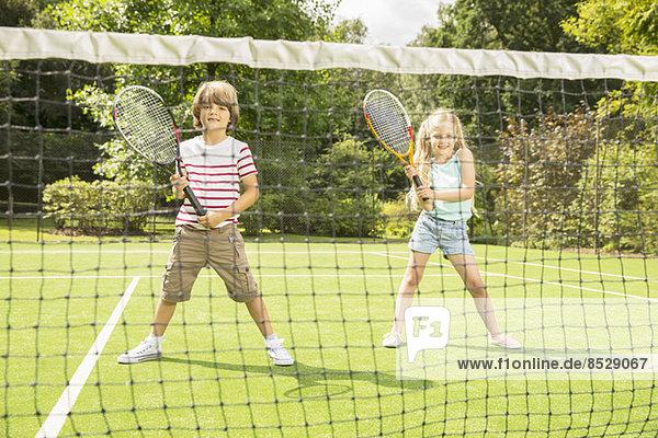 Kinder spielen Tennis auf dem Rasenplatz