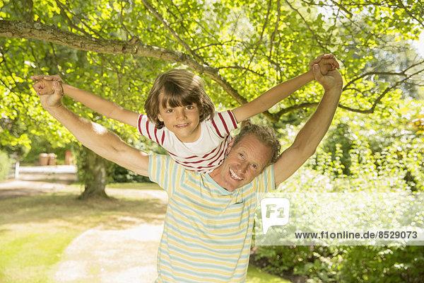 Vater Huckepack-Sohn unter Baum