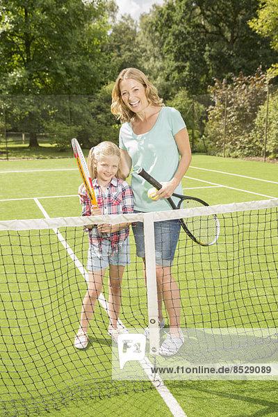 Mutter und Tochter lächeln auf Gras-Tennisplatz