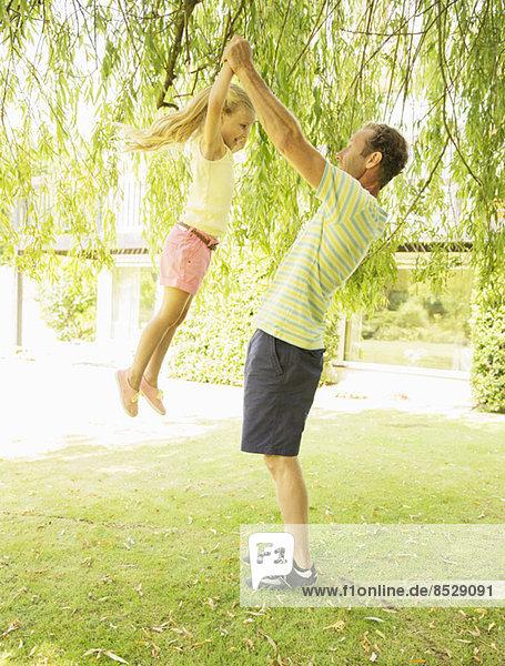 Vater und Tochter spielen im Freien