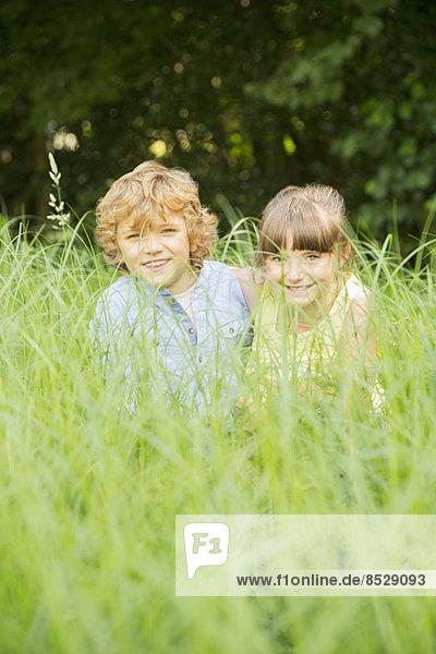 Kinder spielen im hohen Gras