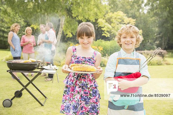 Bruder und Schwester halten gegrillten Mais beim Grillen im Garten