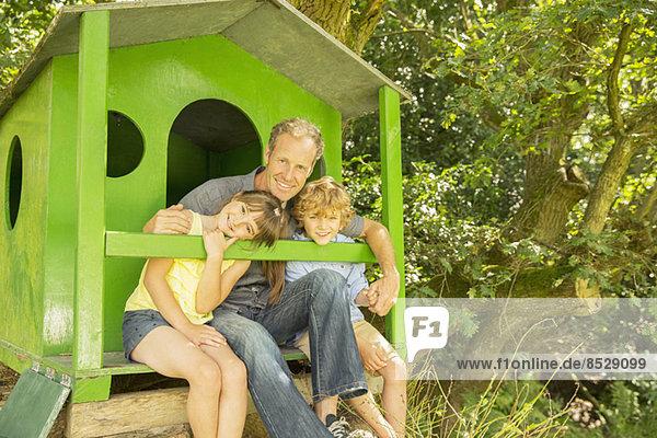 Vater und Kinder entspannen gemeinsam im Baumhaus