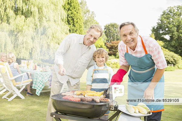 Mehrgenerationen-Männer beim Grillen von Fleisch und Mais im Hinterhof