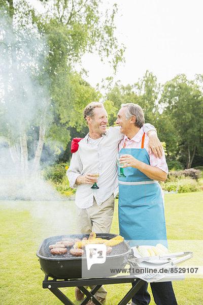 Männer umarmen sich beim Grillen im Garten