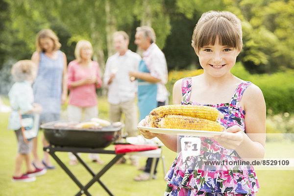 Lächelndes Mädchen mit gegrilltem Mais im Garten