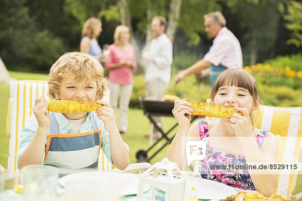 Kinder beim Essen am Tisch im Garten