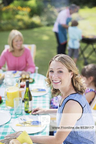 Frau lächelt bei Tisch im Hinterhof
