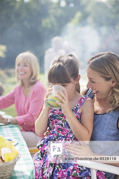 Mädchen trinkt Saft auf Mutters Schoß im Hinterhof