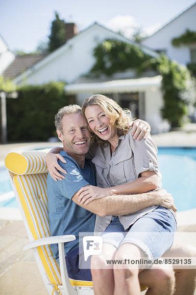 Paar im Sessel am Pool sitzend