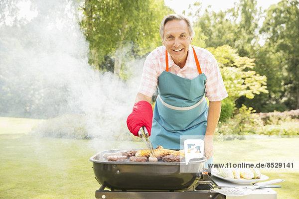 Mann beim Grillen auf dem Grill im Garten