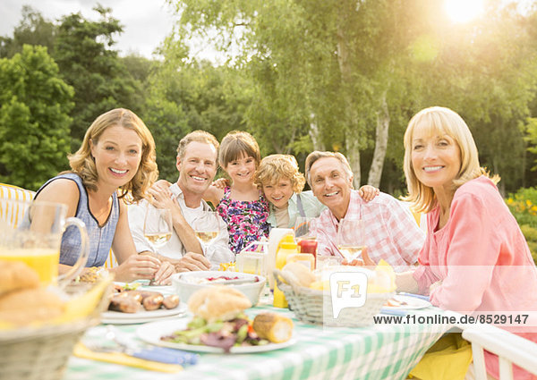 Mehrgenerationen-Familie beim Mittagessen im Hinterhof