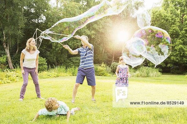 Familienspiel mit großen Blasen im Hinterhof