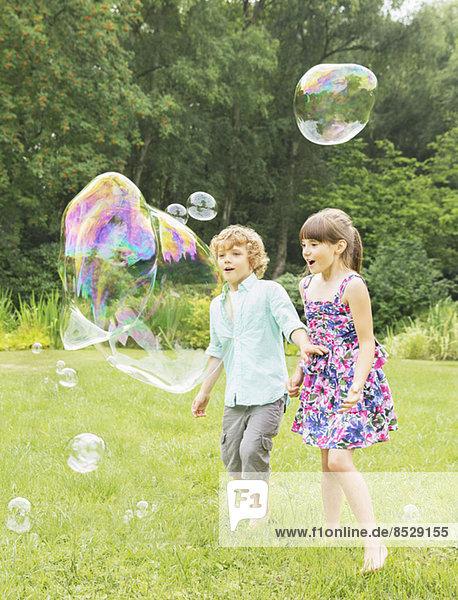 Kinder spielen mit Blasen im Garten